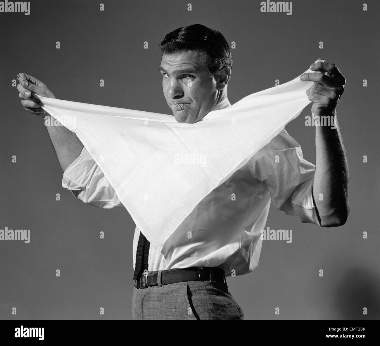 1960s MAN HOLDING CLOTH DIAPER FOLDED IN TRIANGLE UNDER CHIN WITH SAFETY PINS IN MOUTH LOOKING AT CAMERA ANGRILY - Stock Image