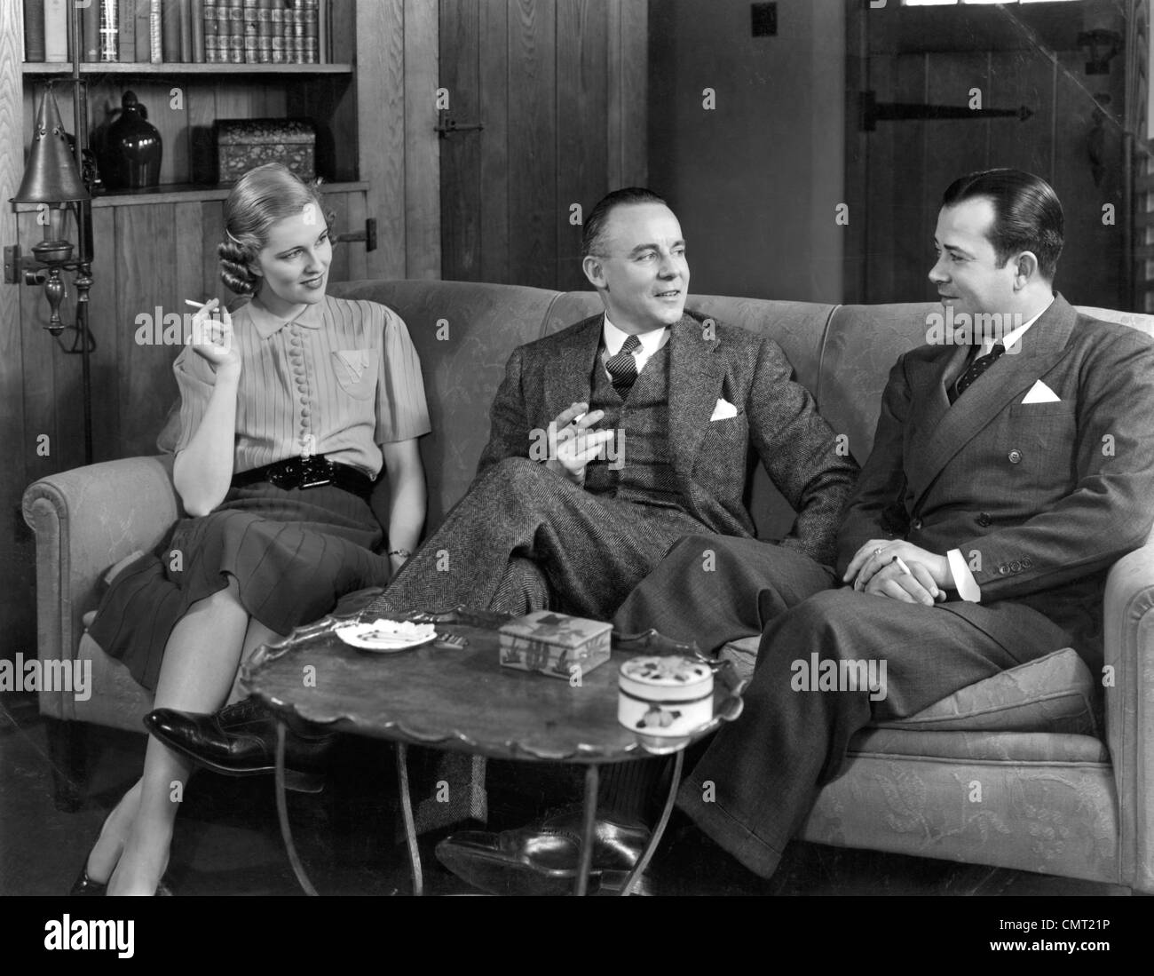 1930s 1940s TWO MEN AND ONE WOMAN SOCIAL GROUP SITTING ON COUCH SMOKING CIGARETTES TALKING - Stock Image