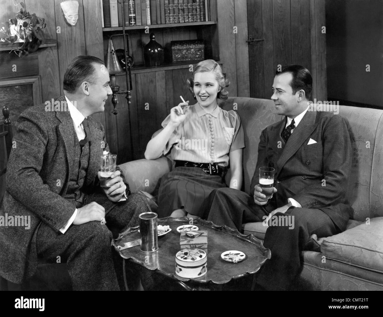 1940s TWO MEN AND ONE WOMAN SOCIAL GROUP SITTING ON COUCH DRINKING BEER SMOKING CIGARETTES TALKING Stock Photo