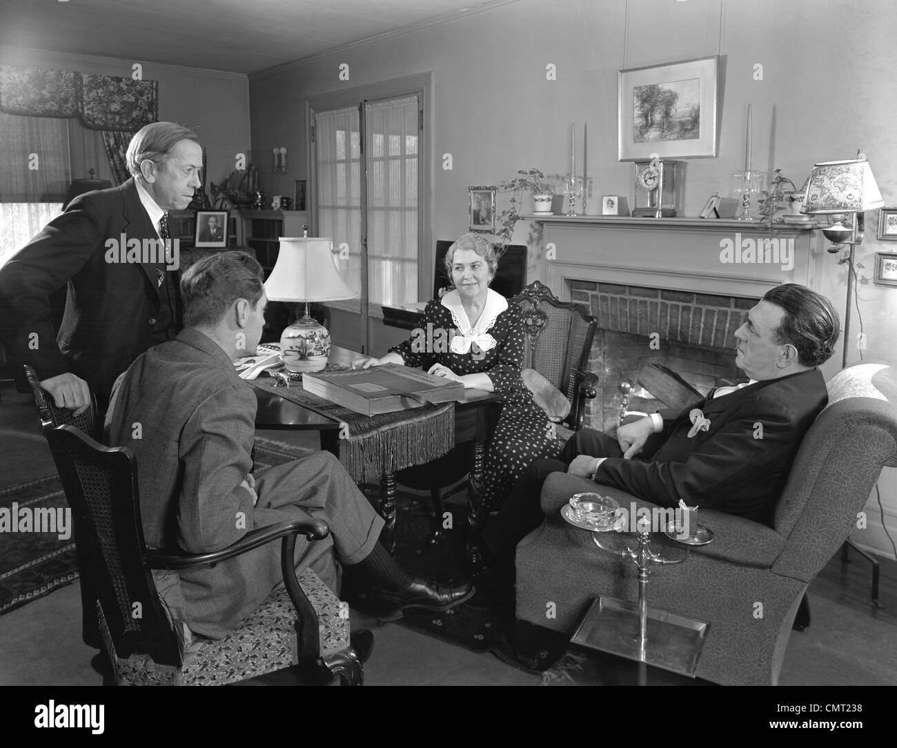 1930s 1940s TWO SALESMEN MAKING SALES PRESENTATION TO OLDER COUPLE HUSBAND AND WIFE SITTING IN LIVING ROOM - Stock Image