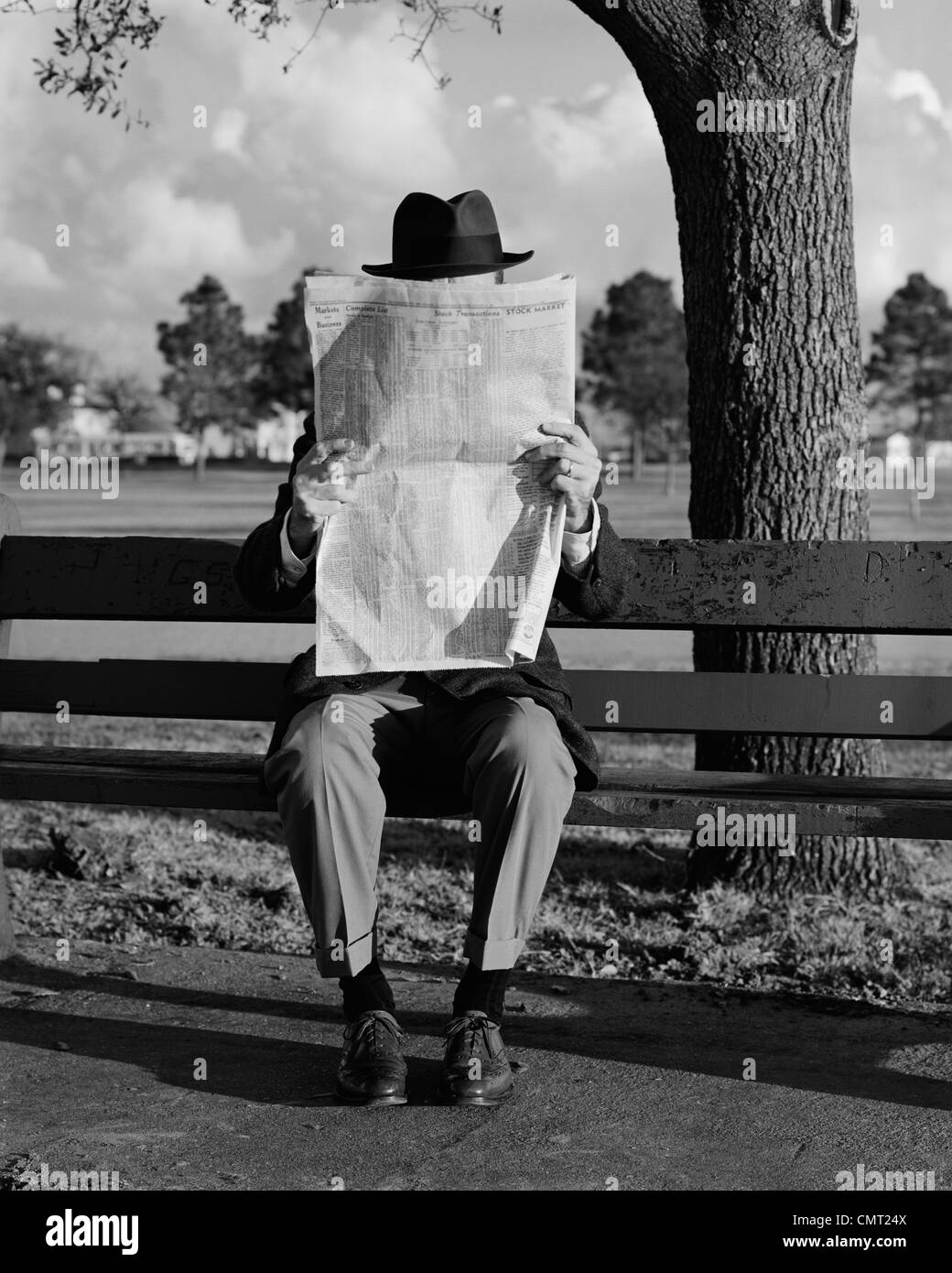 1960s humor portrait man wearing hat sitting on park bench reading