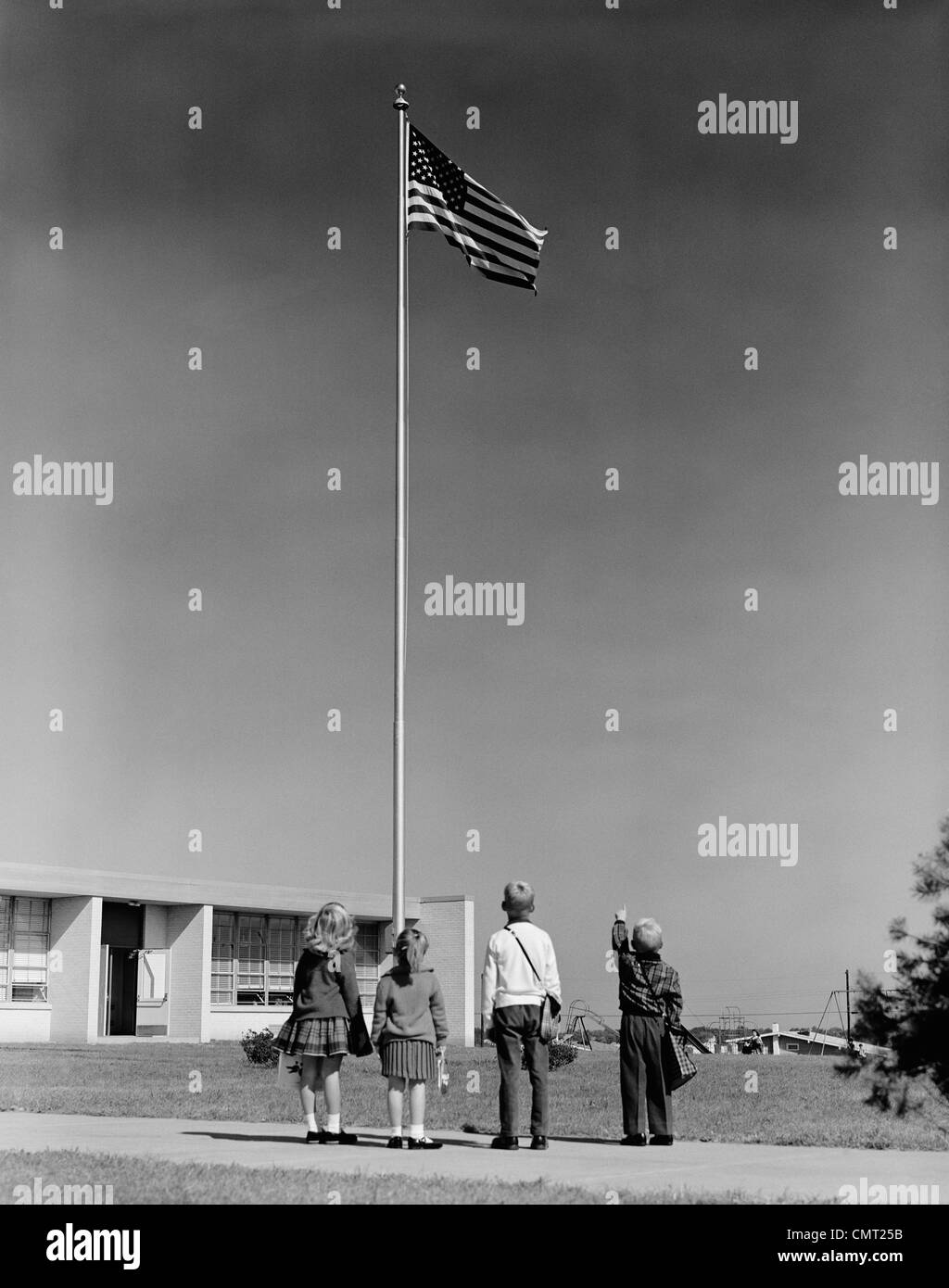 1960s GROUP 4 SCHOOL CHILDREN LOOKING UP AT AMERICAN FLAG - Stock Image