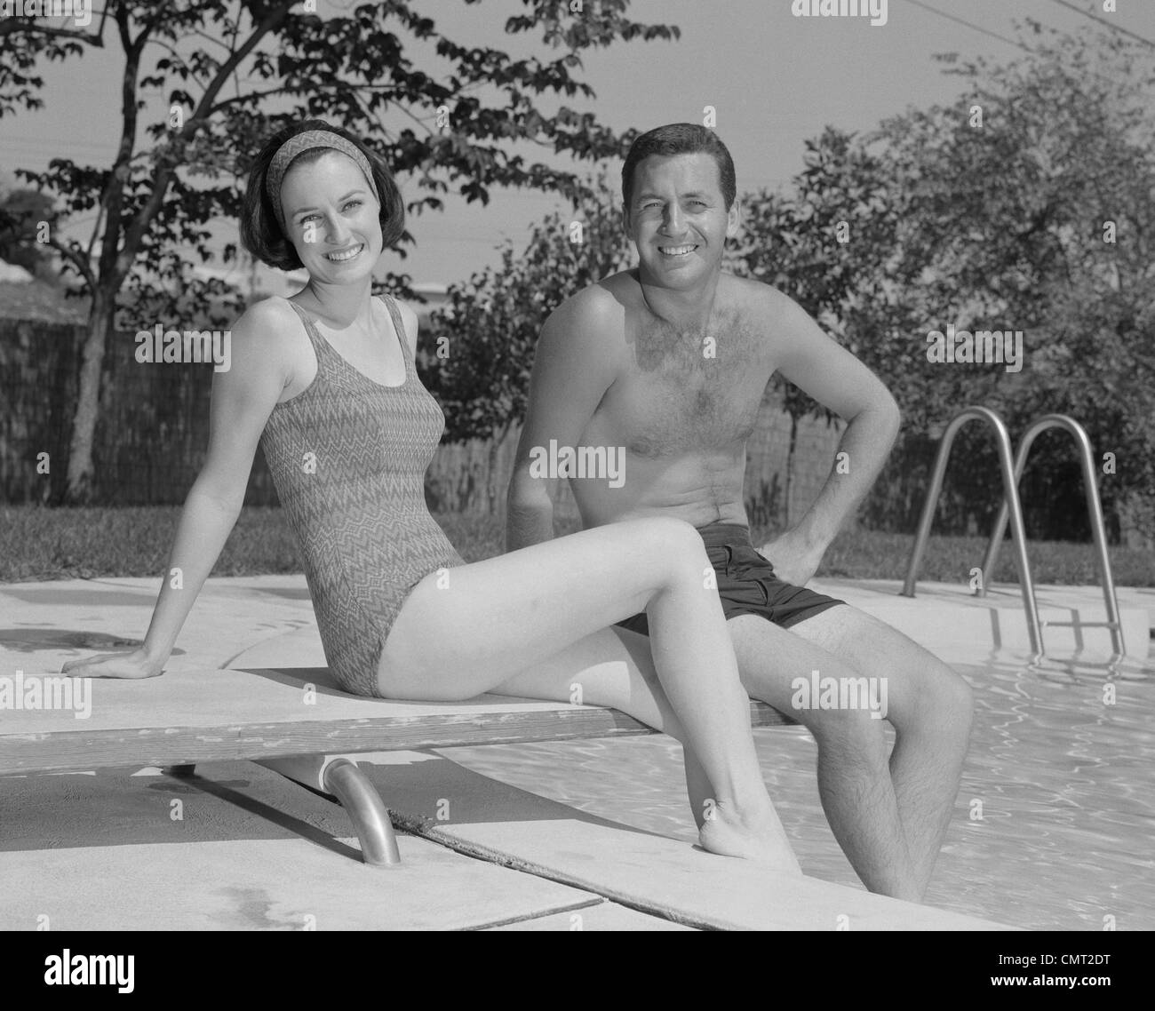7bc8e2e123f75 1960s MAN WOMAN COUPLE SITTING ON DIVING BOARD ON SIDE OF SWIMMING POOL -  Stock Image