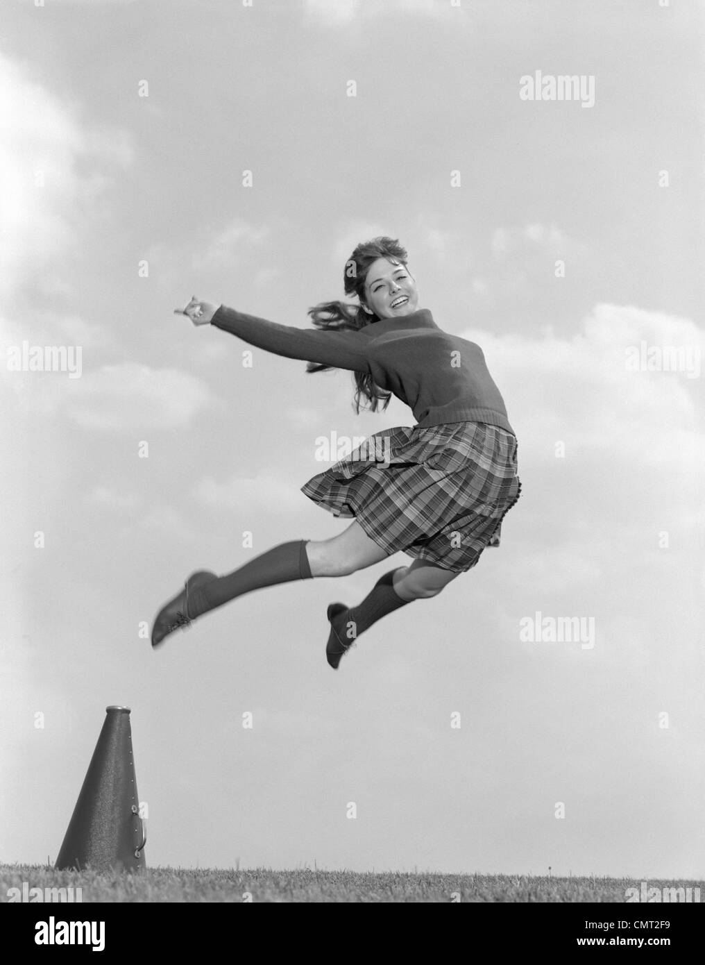 e6b74a8fd 1960s CHEERLEADER IN SWEATER PLAID SKIRT   KNEE SOCKS LEAPING HIGH IN AIR  LOOKING AT CAMERA