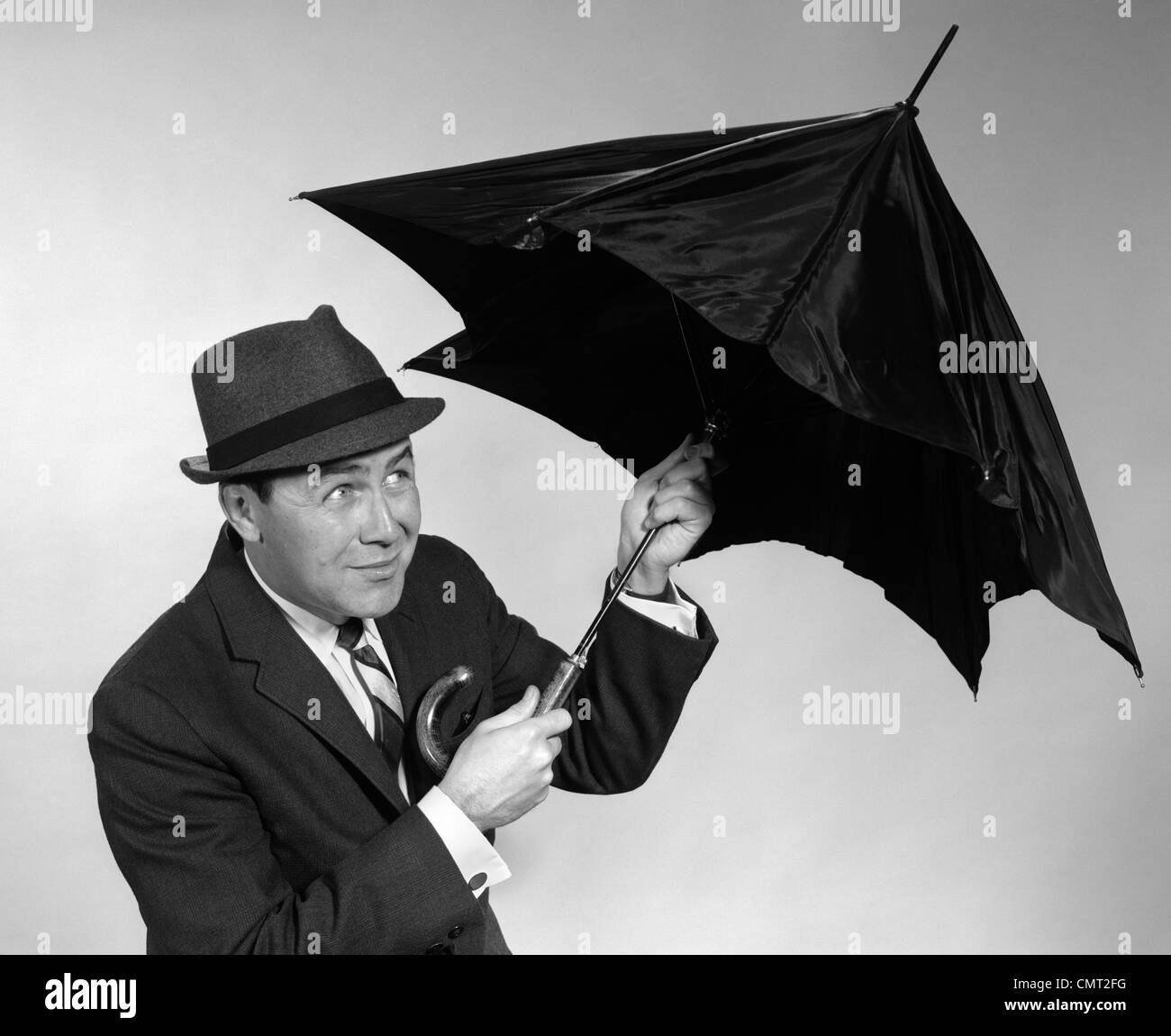1960s BUSINESSMAN OPENING UP UMBRELLA - Stock Image