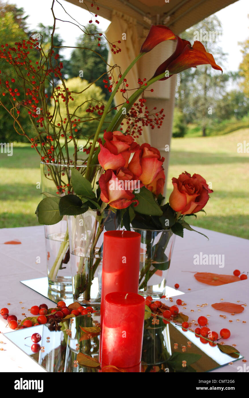 White wedding gazebo with red flowers and candles decoration in a ...