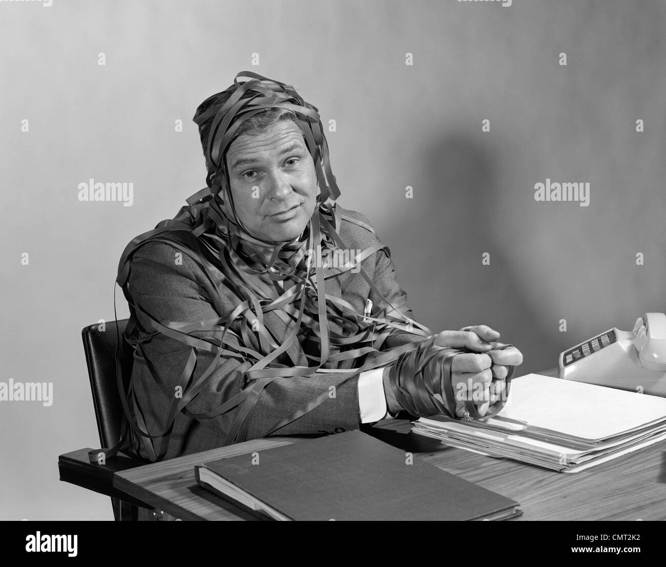 1960s BUSINESSMAN AT DESK HANDS AND TORSO WRAPPED IN TYPEWRITER RIBBON RED TAPE LOOKING AT CAMERA - Stock Image
