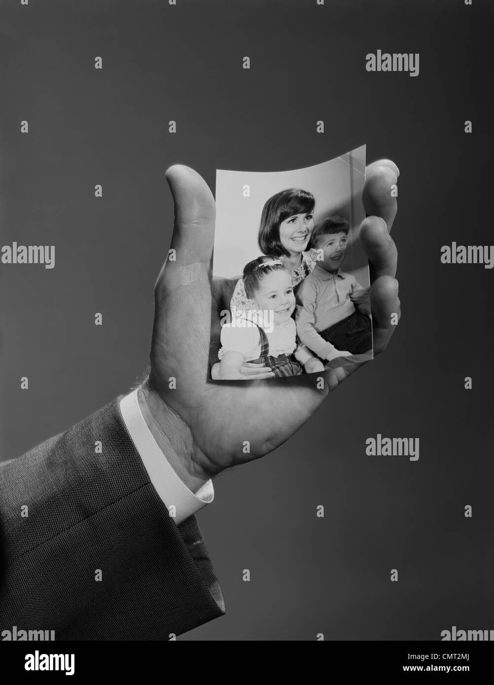 1960s MALE HAND HOLDING FAMILY PHOTO - Stock Image