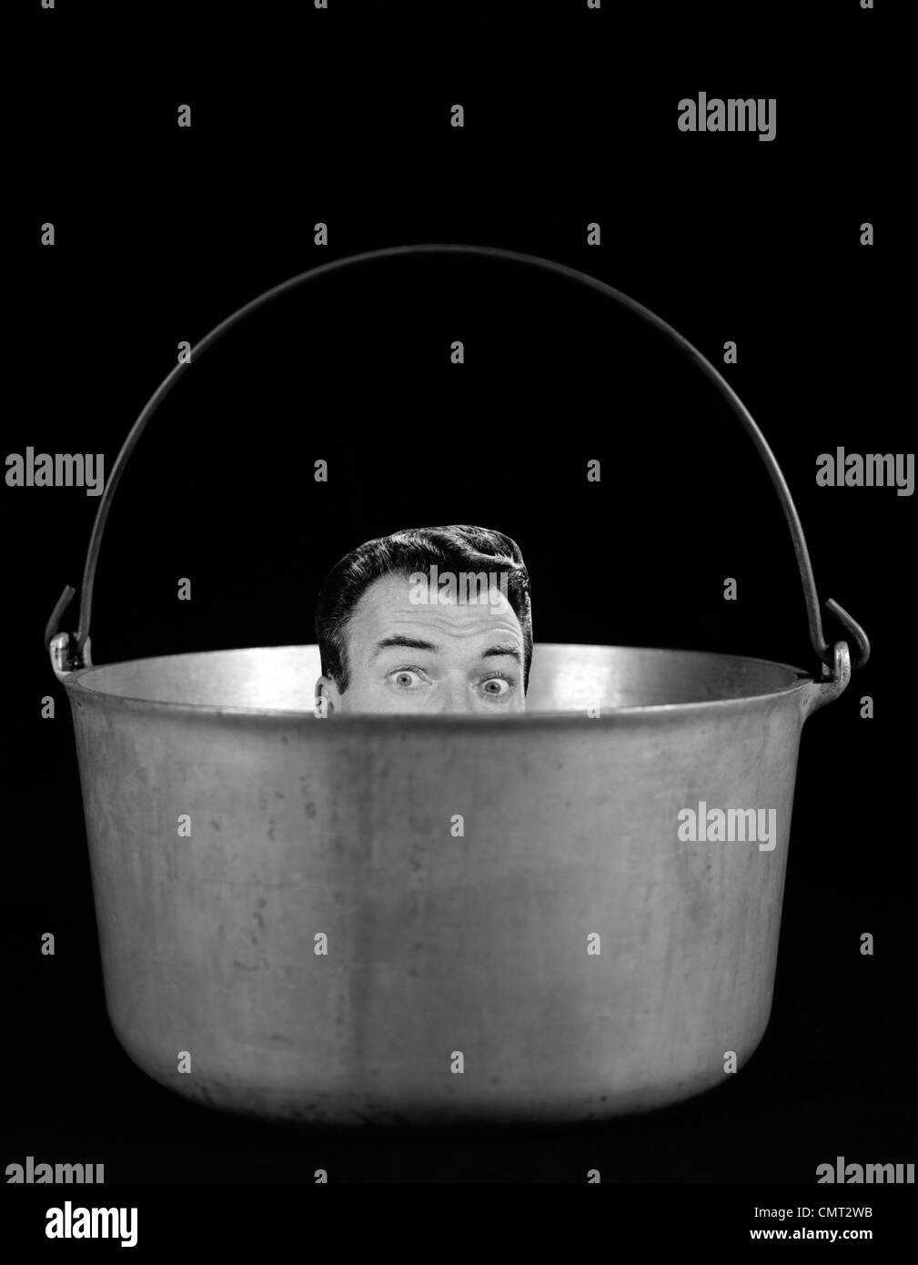 1950s 1960s SYMBOLIC MONTAGE PORTRAIT MAN IN THE SOUP LOOKING WIDE EYED FROM INSIDE THE KETTLE Stock Photo