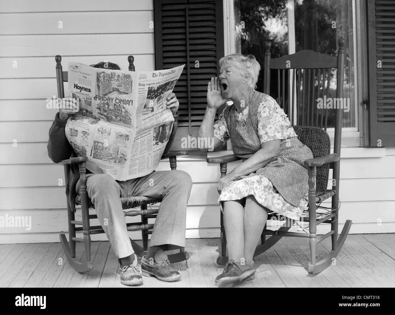 1970s ELDERLY COUPLE IN ROCKING CHAIRS ON PORCH MAN READING NEWSPAPER WHILE WIFE HOLLERS AT HIM Stock Photo
