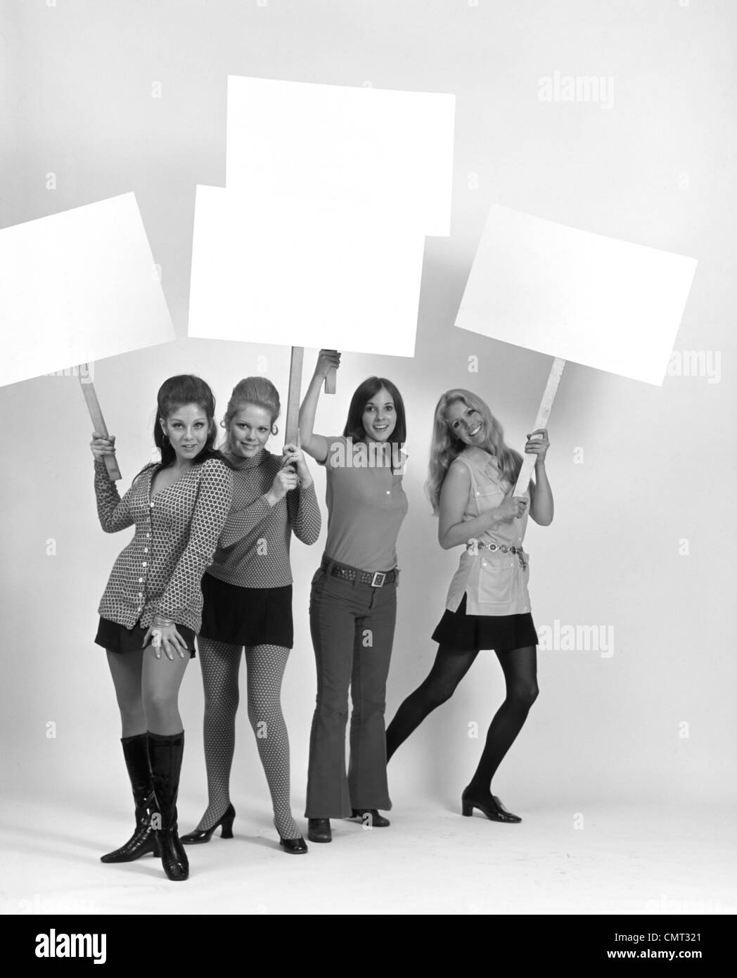 5888516d8c 1970s FOUR YOUNG WOMEN WEARING MINISKIRTS AND FLARED JEANS CARRYING BLANK  SIGNS - Stock Image