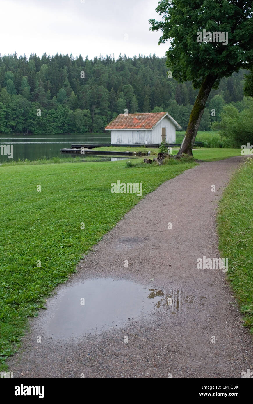 Tranquil scene of greenery and boathouse - Stock Image