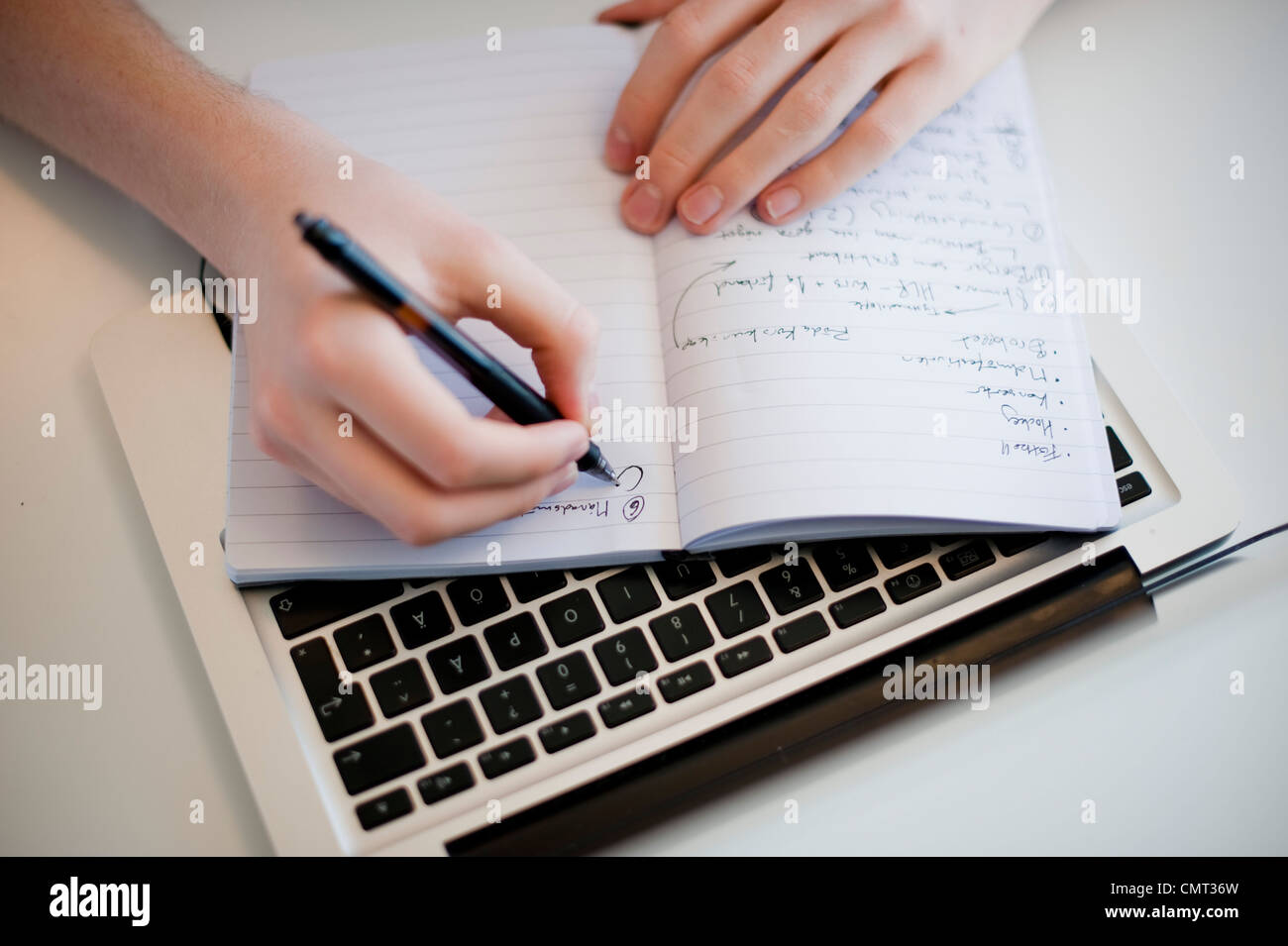 Close-up of human hand writing in notebook - Stock Image