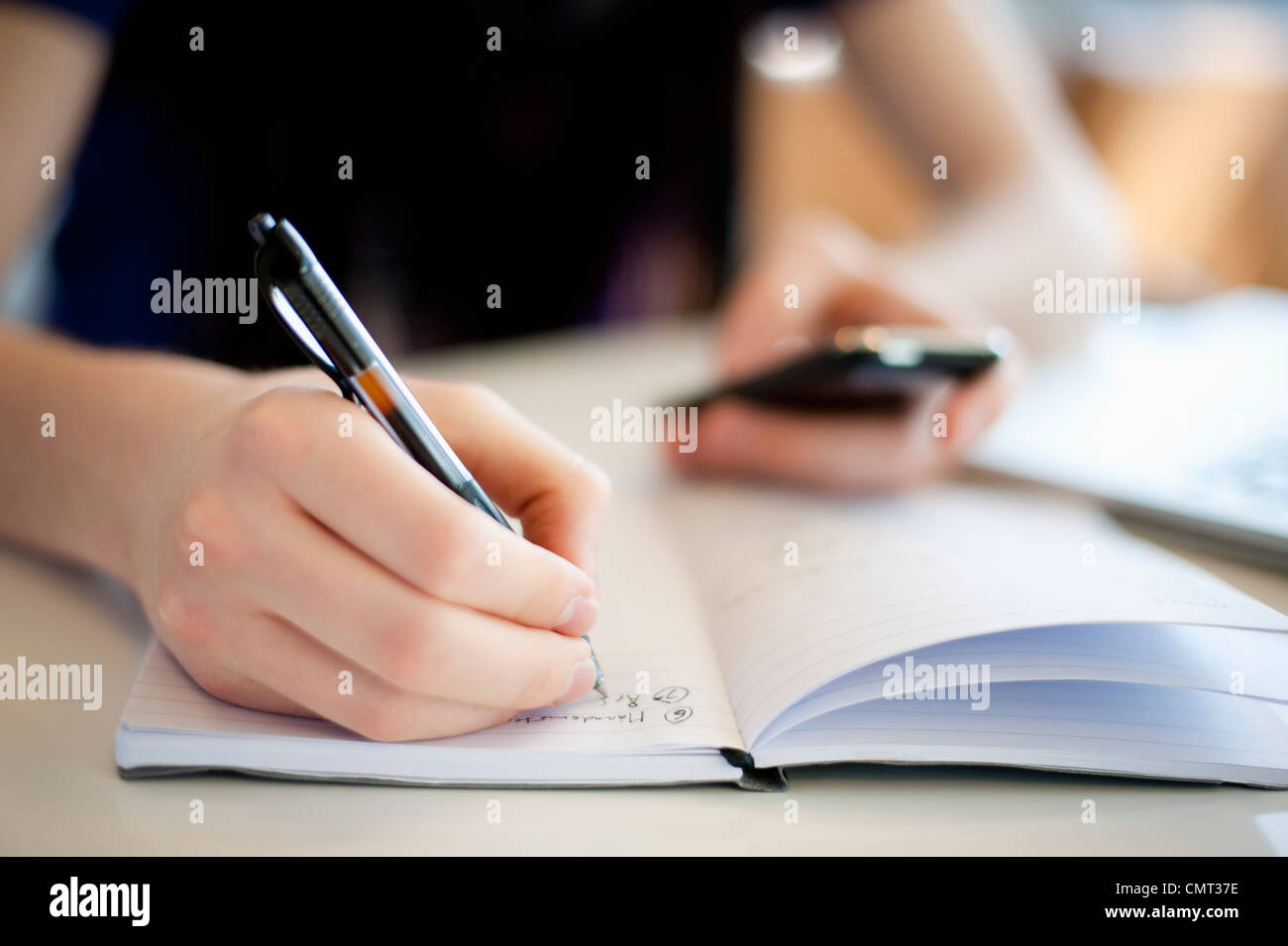 Close-up of human hand writing and holding mobile phone - Stock Image