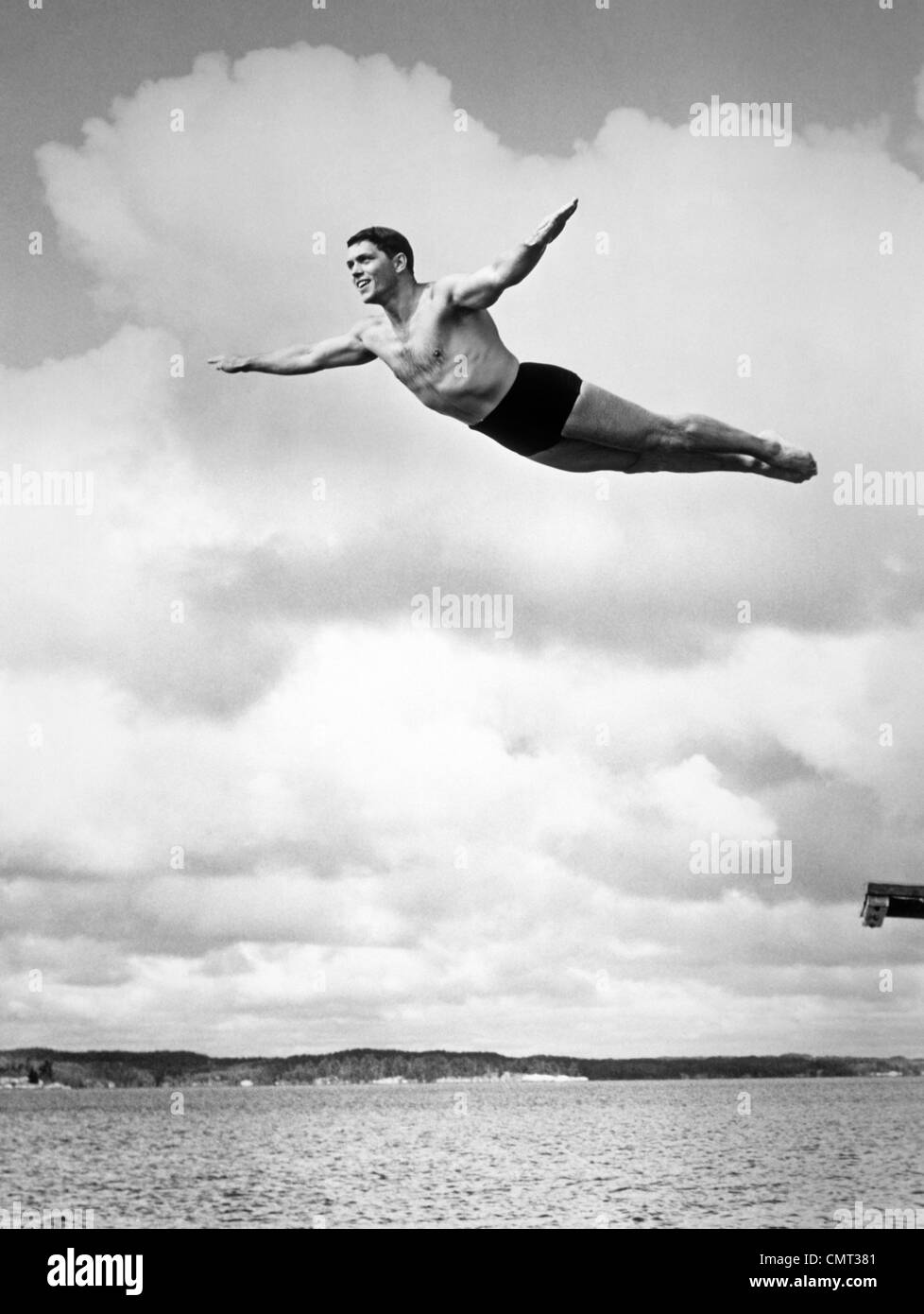 1930s MAN SWAN DIVING FROM HIGH DIVING BOARD OUTDOOR - Stock Image