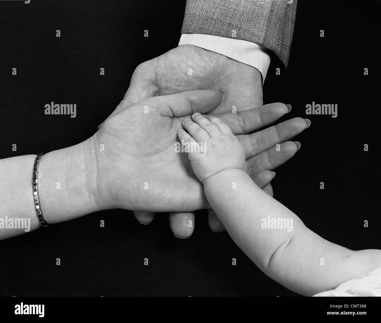 1950s HANDS OF FAMILY MAN WOMAN CHILD MOTHER FATHER BABY - Stock Image