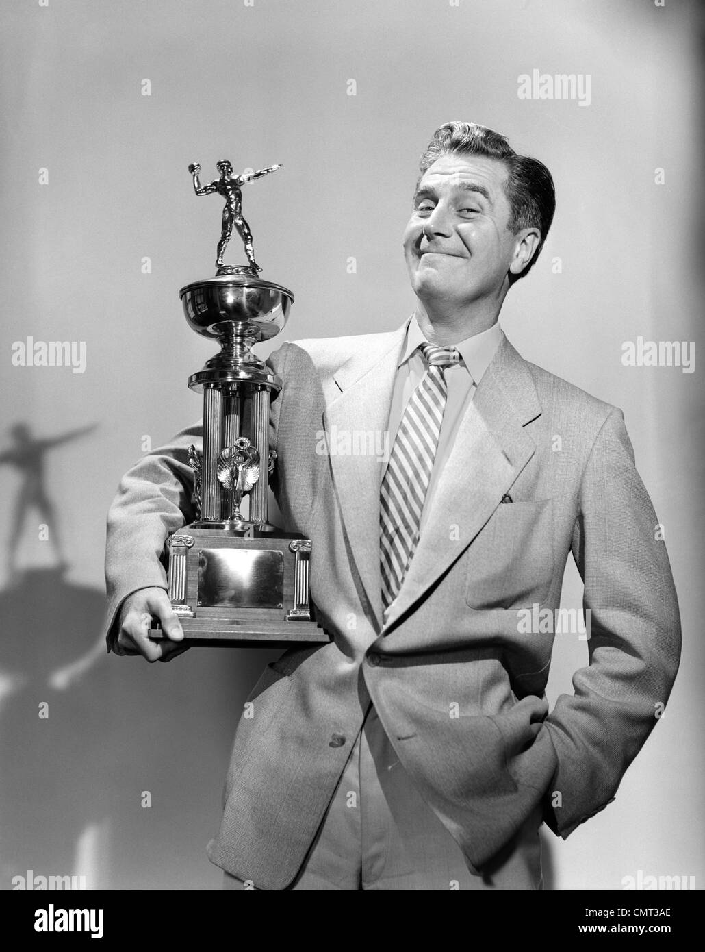 1950s 1960s PROUD MAN SMILING HOLDING A FOOTBALL TROPHY LOOKING AT CAMERA - Stock Image