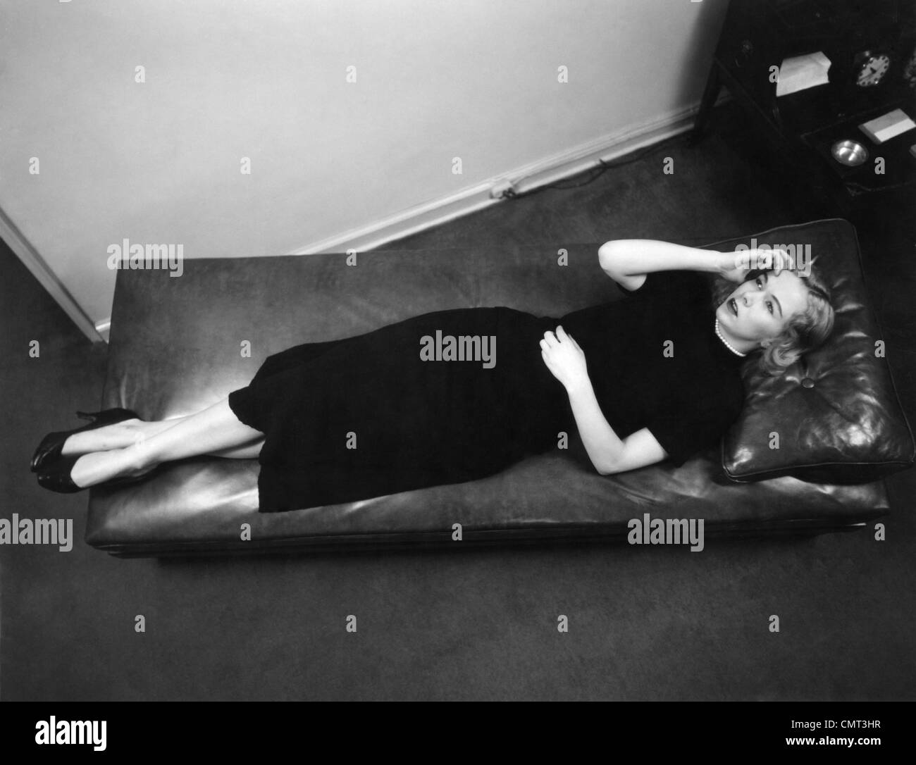 1950s WORRIED WOMAN HAND TO FOREHEAD SEEN FROM ABOVE LYING DOWN ON PSYCHIATRIST THERAPY COUCH - Stock Image