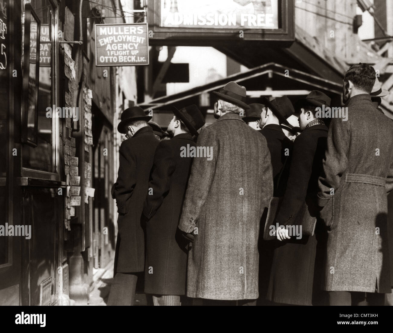 1930s GREAT DEPRESSION COLD MEN STANDING IN EMPLOYMENT LINE LOOKING FOR WORK Stock Photo