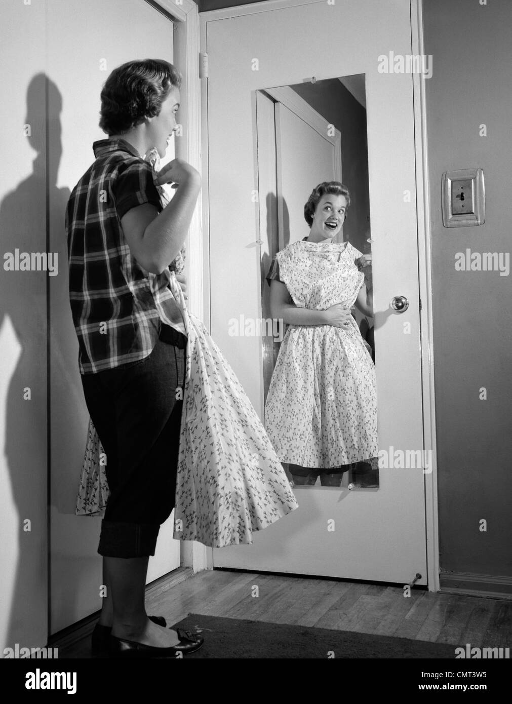 1950s Teen Girl In Jeans Holding Formal Dress Up To Chest
