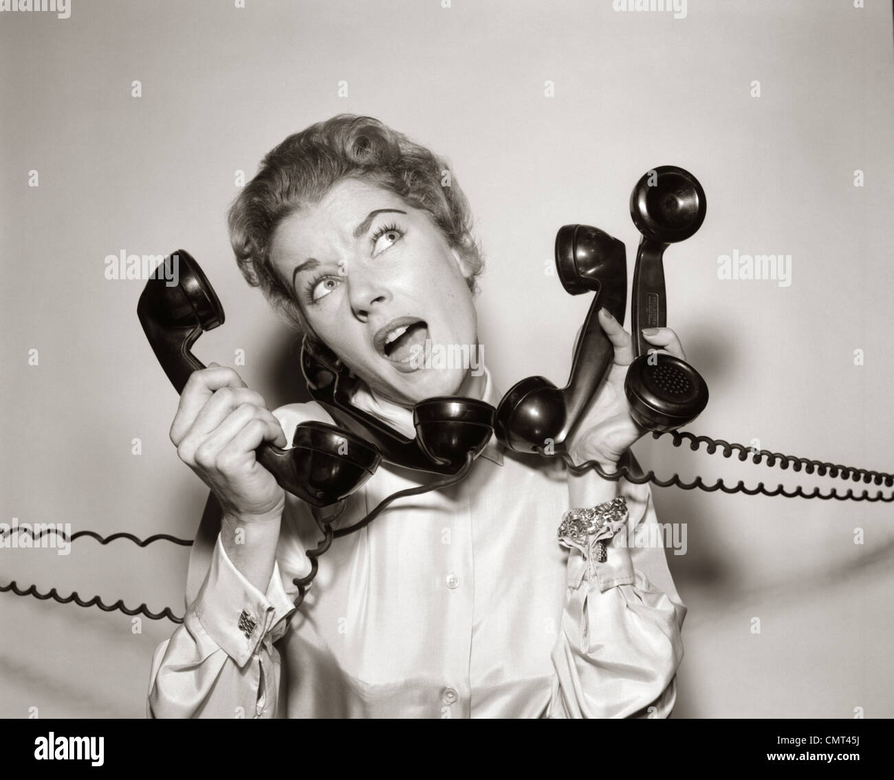 1950s 1960s OVERWHELMED STRESSED WOMAN HOLDING ANSWERING FOUR BLACK TELEPHONE PHONE RECEIVERS AT ONE TIME - Stock Image