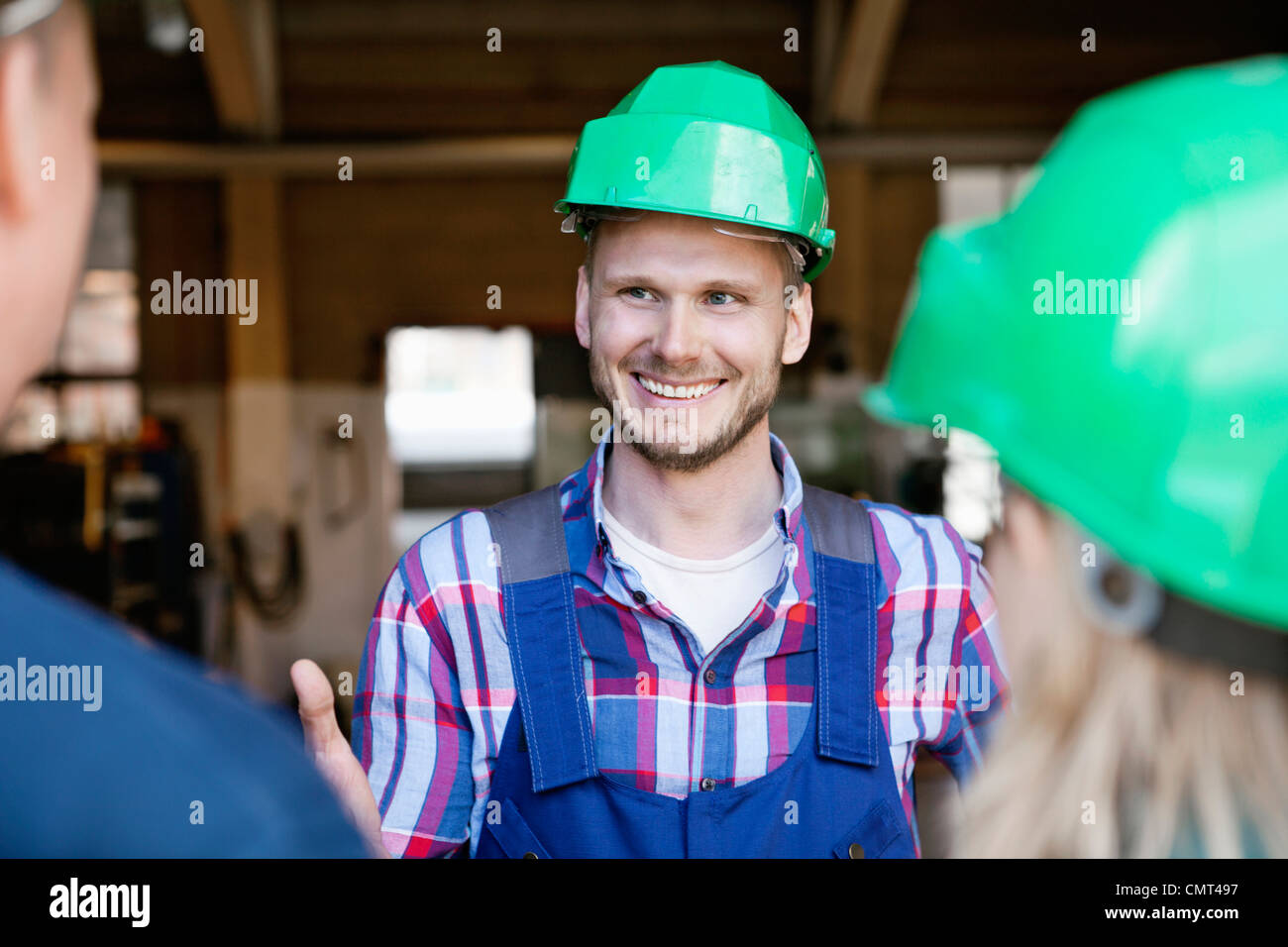 Industrial workers having a conversation - Stock Image