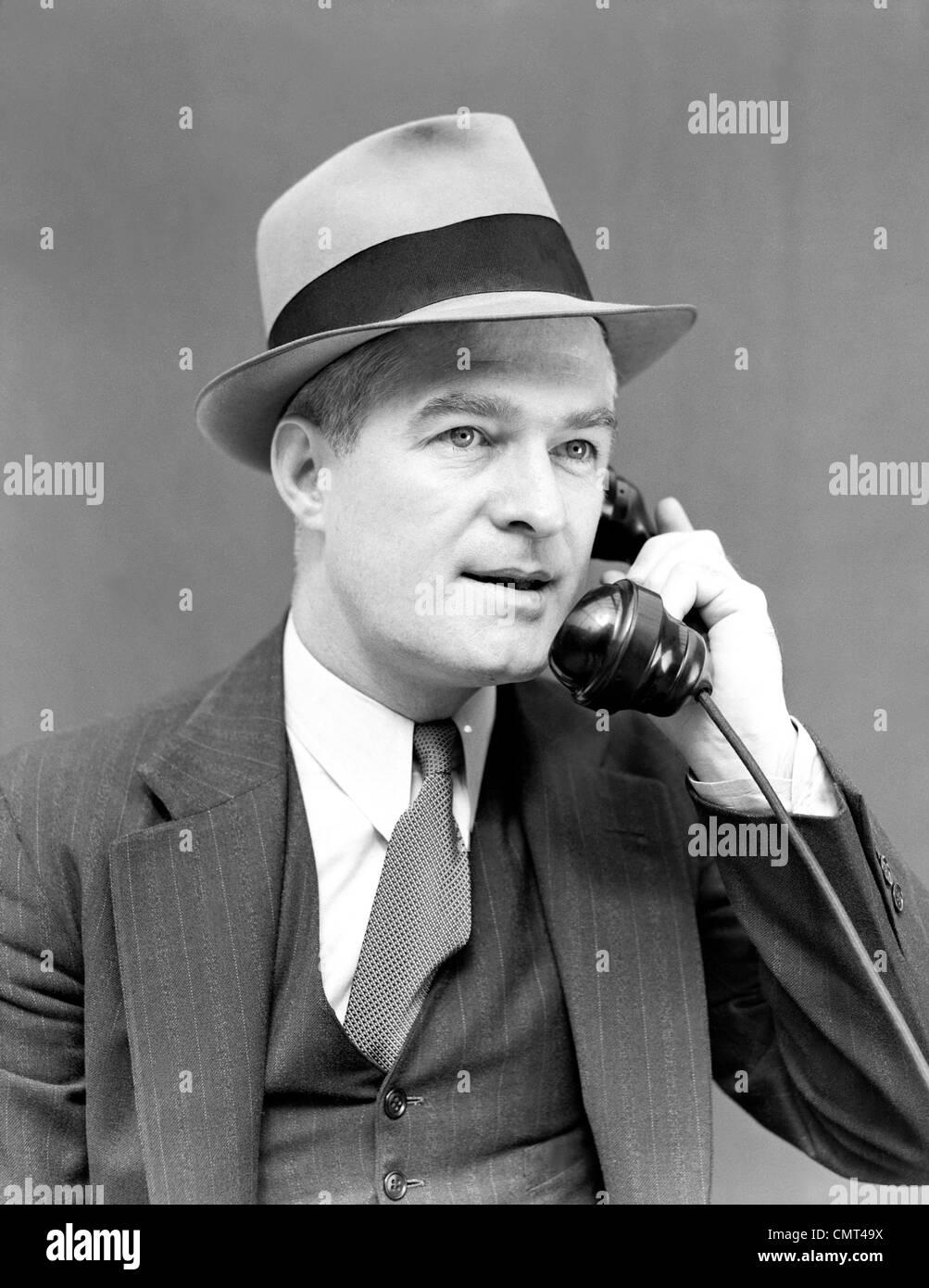 fa0d869edd2a3 1930s 1940s MAN WEARING HAT SUIT   VEST   NECKTIE TALKING ON TELEPHONE  SERIOUS EXPRESSION PORTRAIT