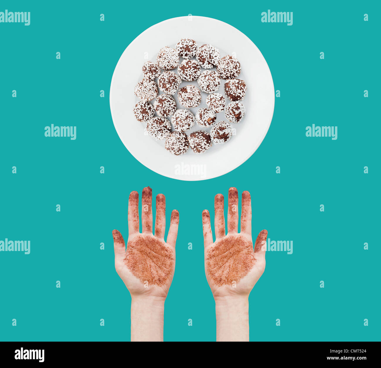 Messy hands and chocolate balls - Stock Image