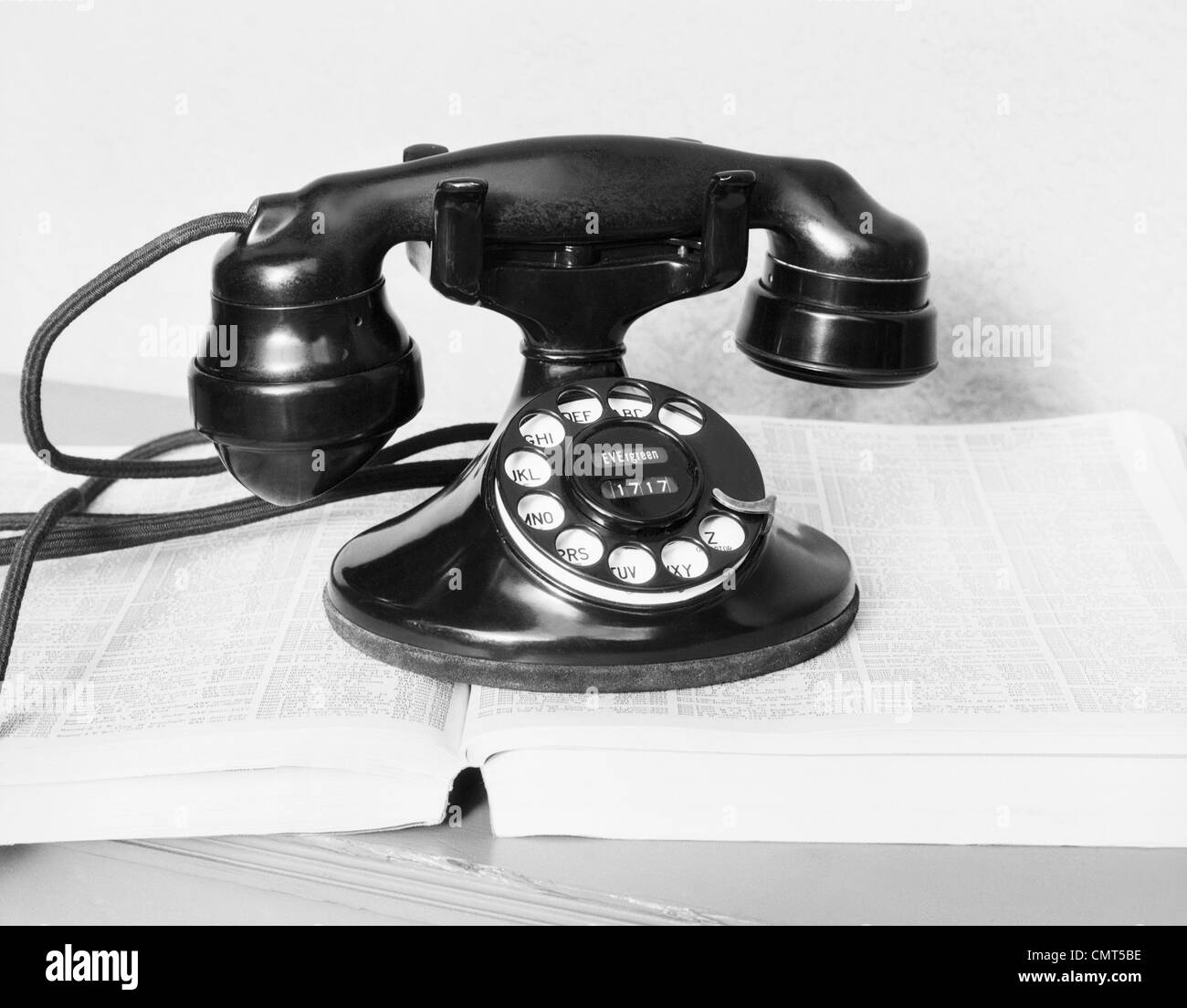 1930s OLD BLACK ROTARY DIAL CRADLE TELEPHONE ON OPEN TELEPHONE NUMBER DIRECTORY BOOK - Stock Image
