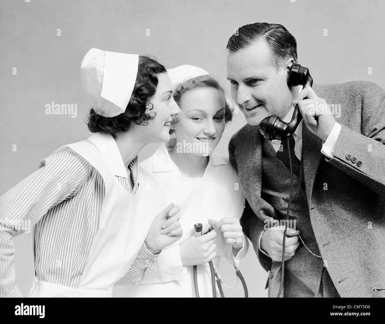 1930s SMILING MAN IN SUIT NEW FATHER WITH TWO WOMEN NURSES TALKING GOOD NEWS ON TELEPHONE HOSPITAL MEDICAL SITUATION - Stock Image