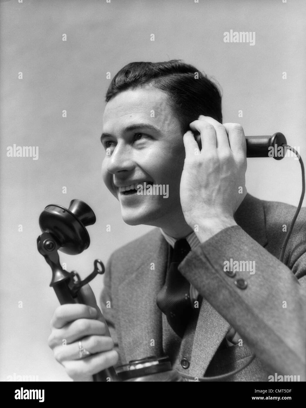 1920s 1930s MAN TALKING ON CANDLESTICK PHONE - Stock Image