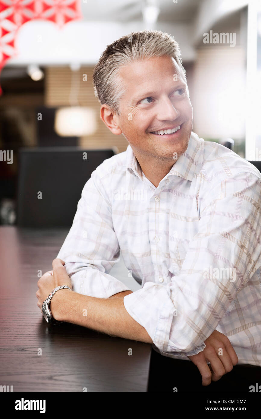 Happy businessman in checked shirt looking away - Stock Image