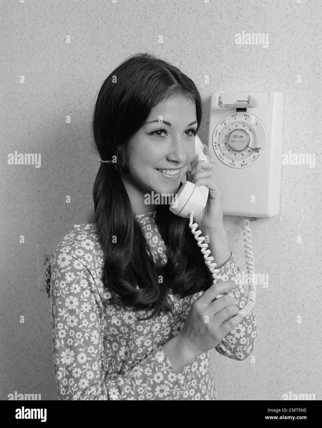 1960s 1970s SMILING TEENAGE GIRL TALKING ON ROTARY WALL TELEPHONE - Stock Image