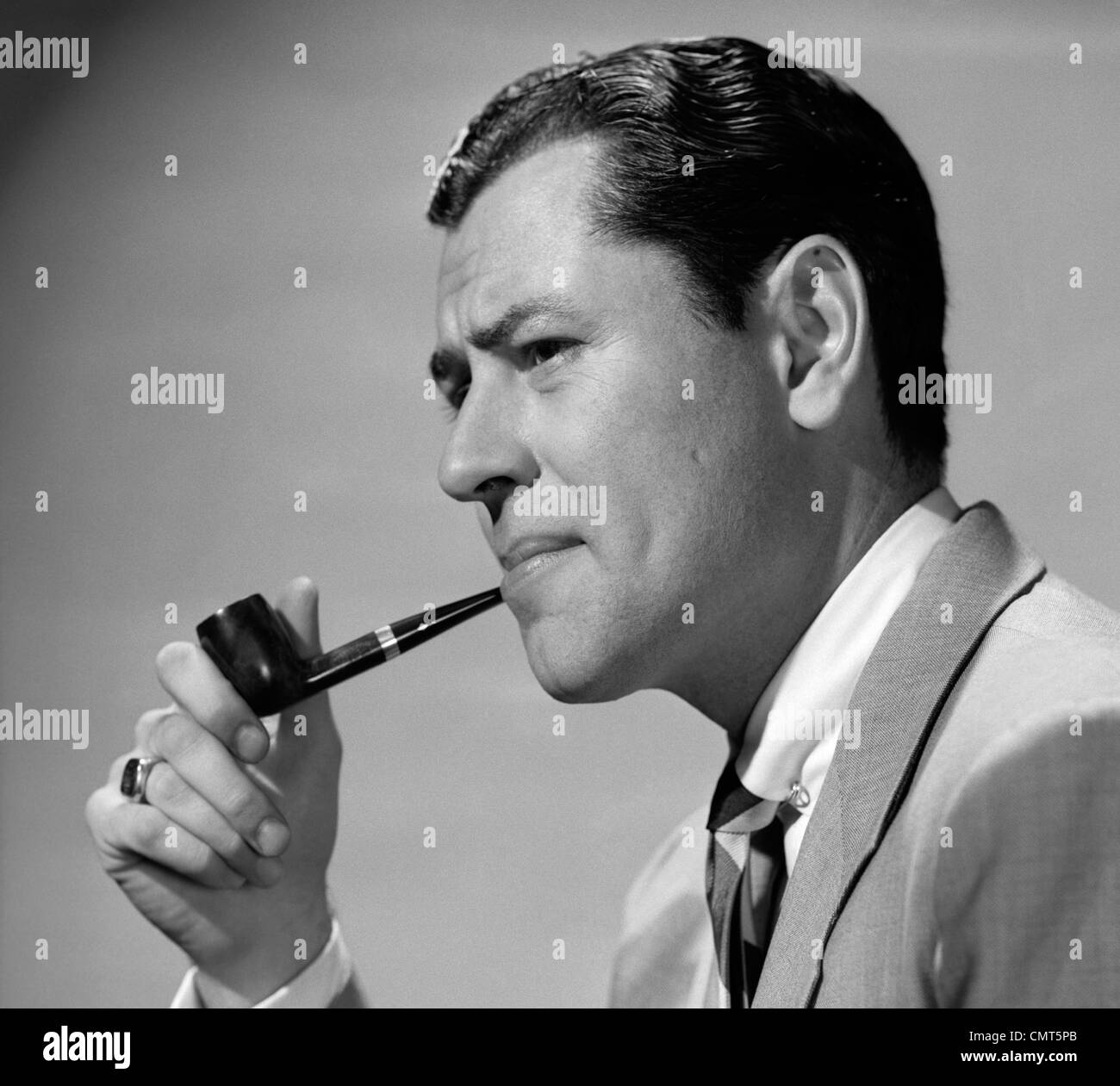 1950s FROWNING BUSINESSMAN IN JACKET AND TIE SMOKING A PIPE - Stock Image
