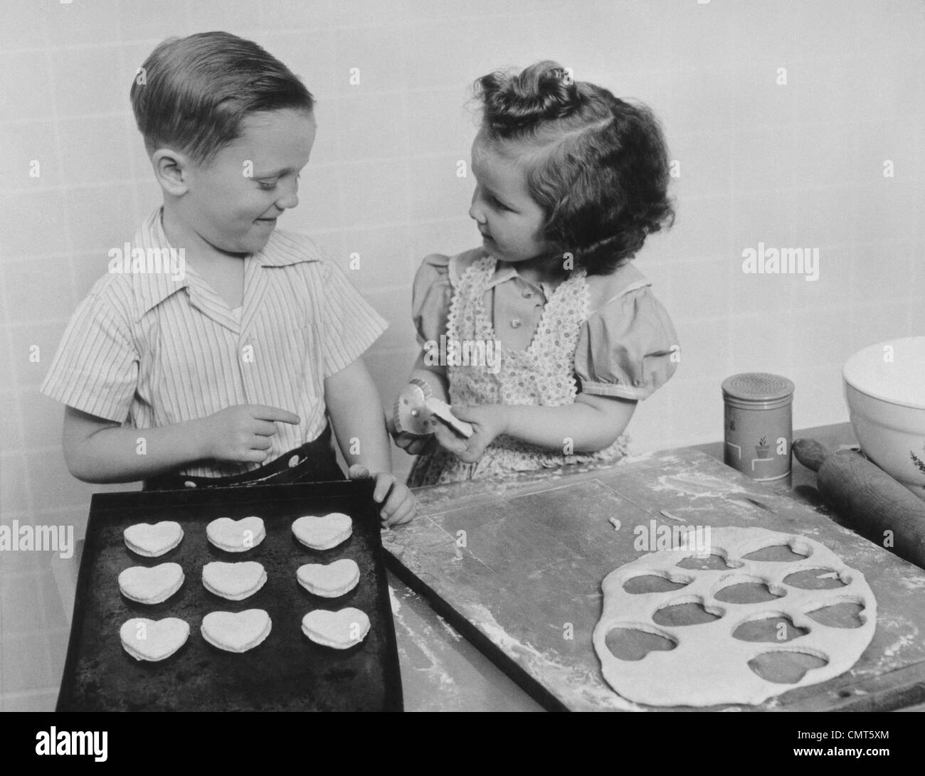 1940s YOUNG SMILING GIRL AND BOY BAKING HEART SHAPED VALENTINE COOKIES - Stock Image