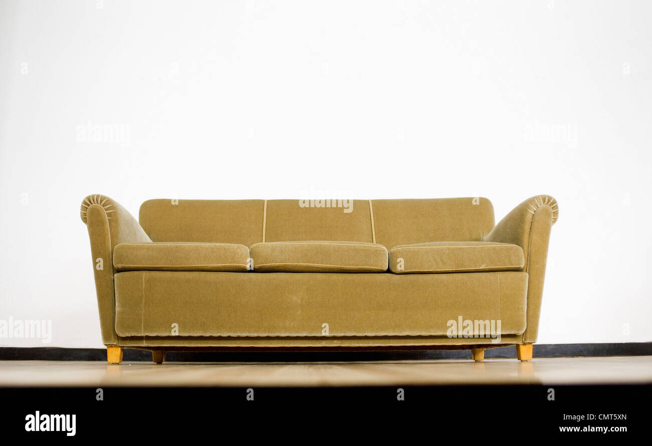 Green sofa against white background - Stock Image