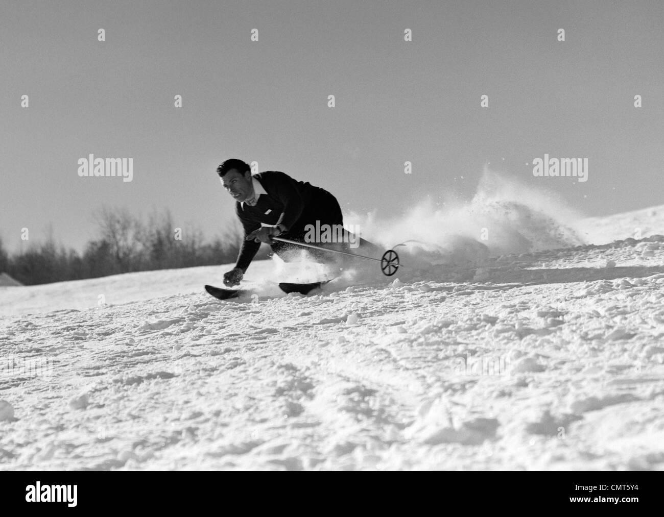 1940s MAN SKIING DOWNHILL RACING FAST SNOW FLYING WINTER OUTDOOR - Stock Image