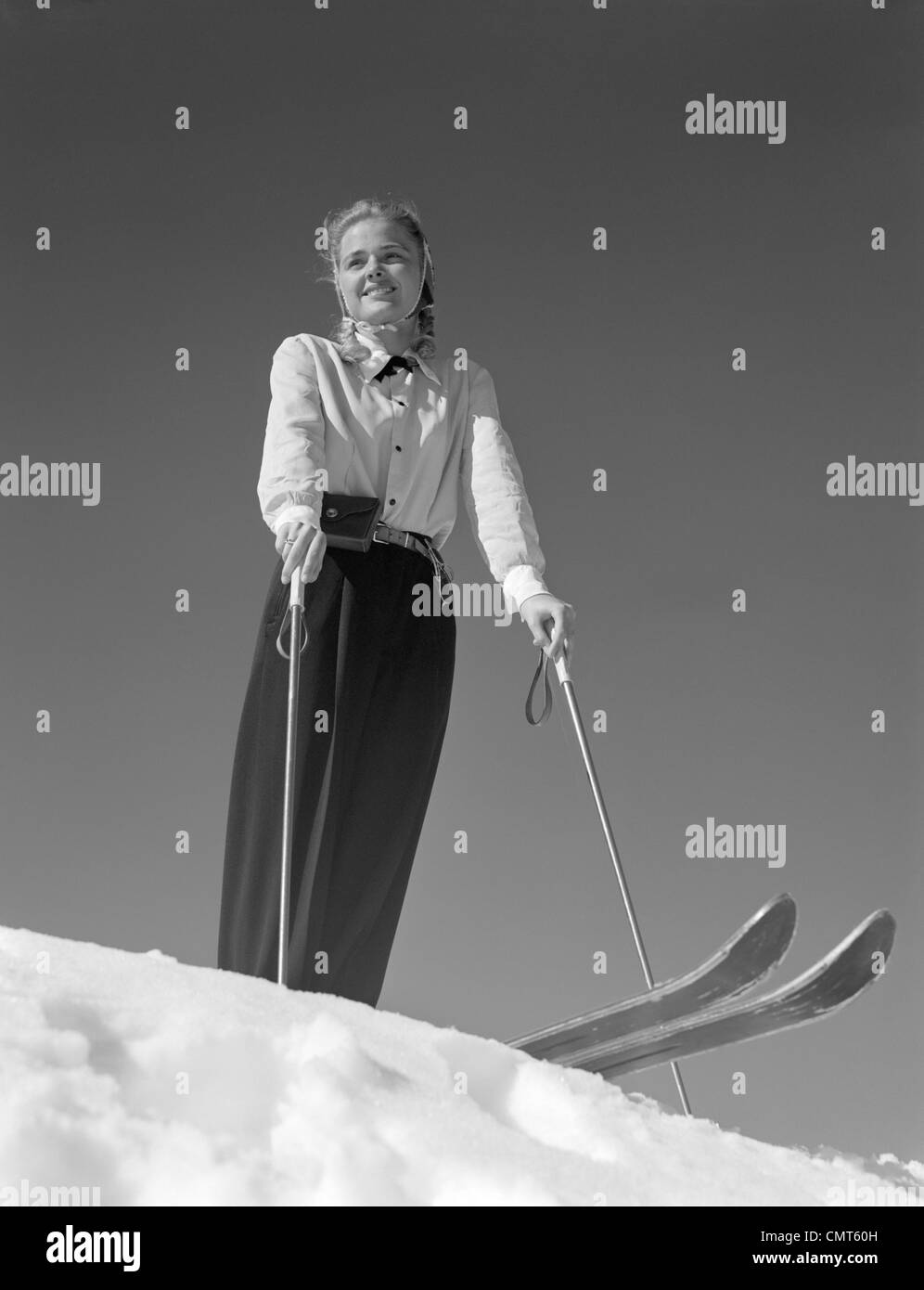 1940s SMILING BLOND WOMAN SKIER POISED ON HILL TOP TO BEGIN DOWNHILL SKIING WINTER OUTDOOR - Stock Image