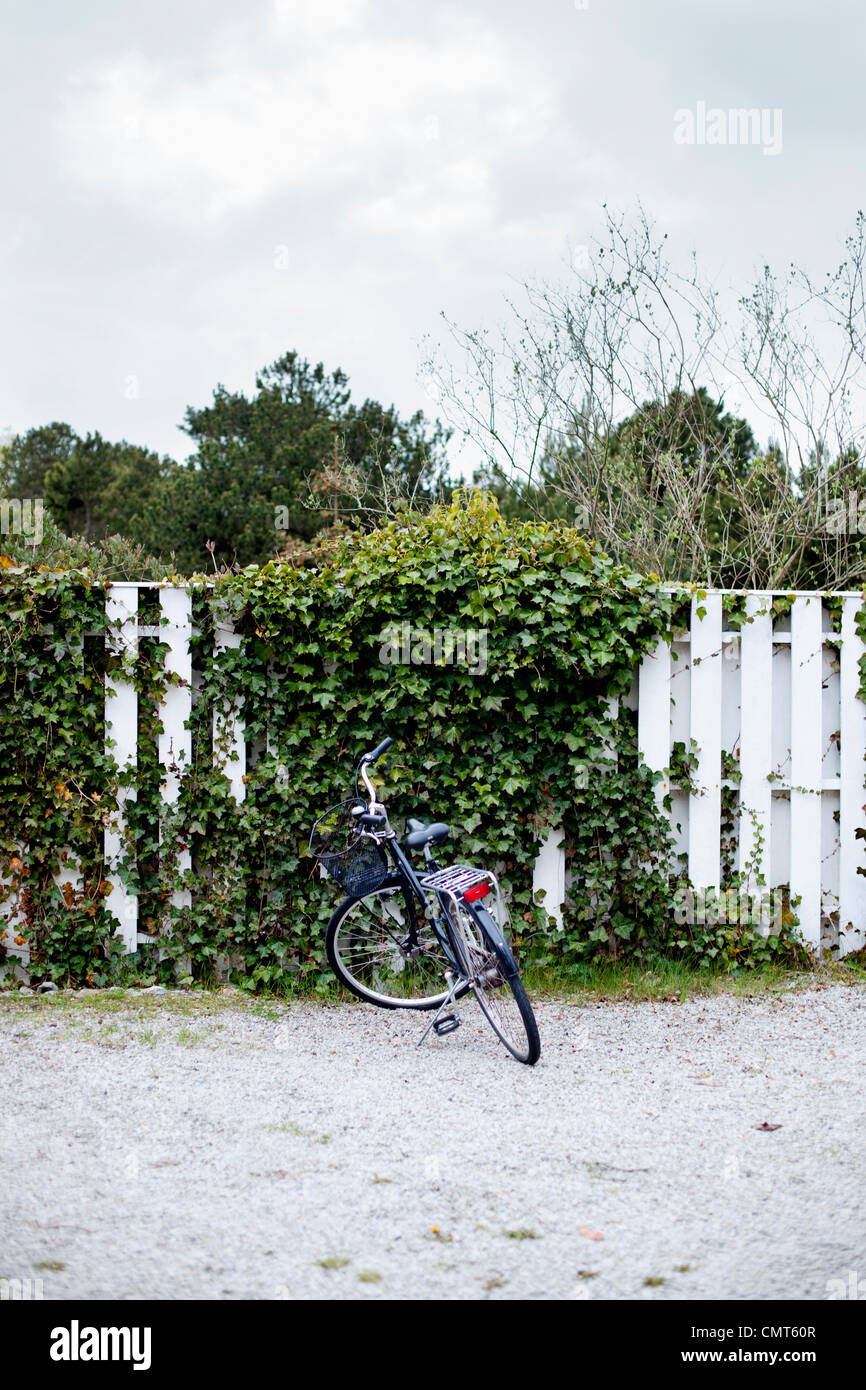 Bicycle parked near fence - Stock Image
