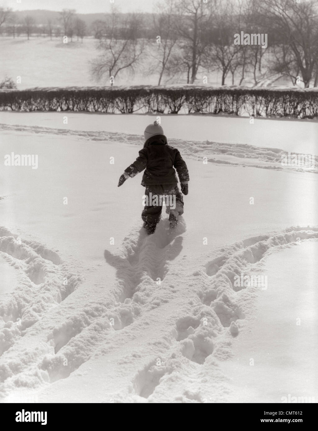 1950s BACK VIEW CHILD IN SNOWSUIT MAKING TRACKS IN FRESH SNOW OUTDOOR - Stock Image