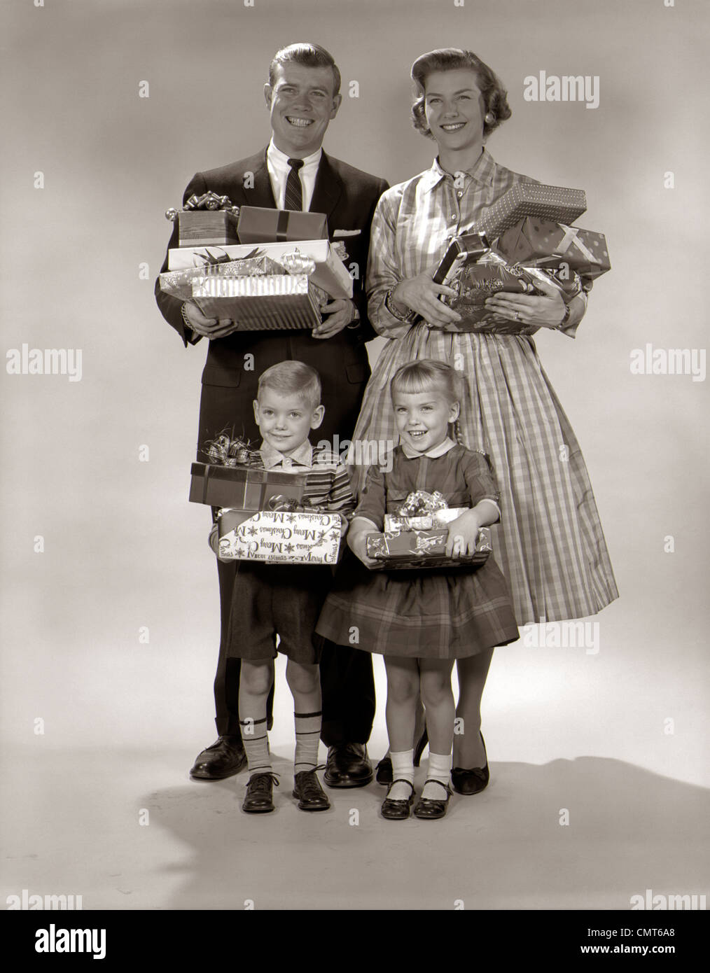 1960s FAMILY PORTRAIT OF FOUR MOTHER FATHER BOY GIRL CARRYING CHRISTMAS GIFTS WRAPPED PRESENTS - Stock Image