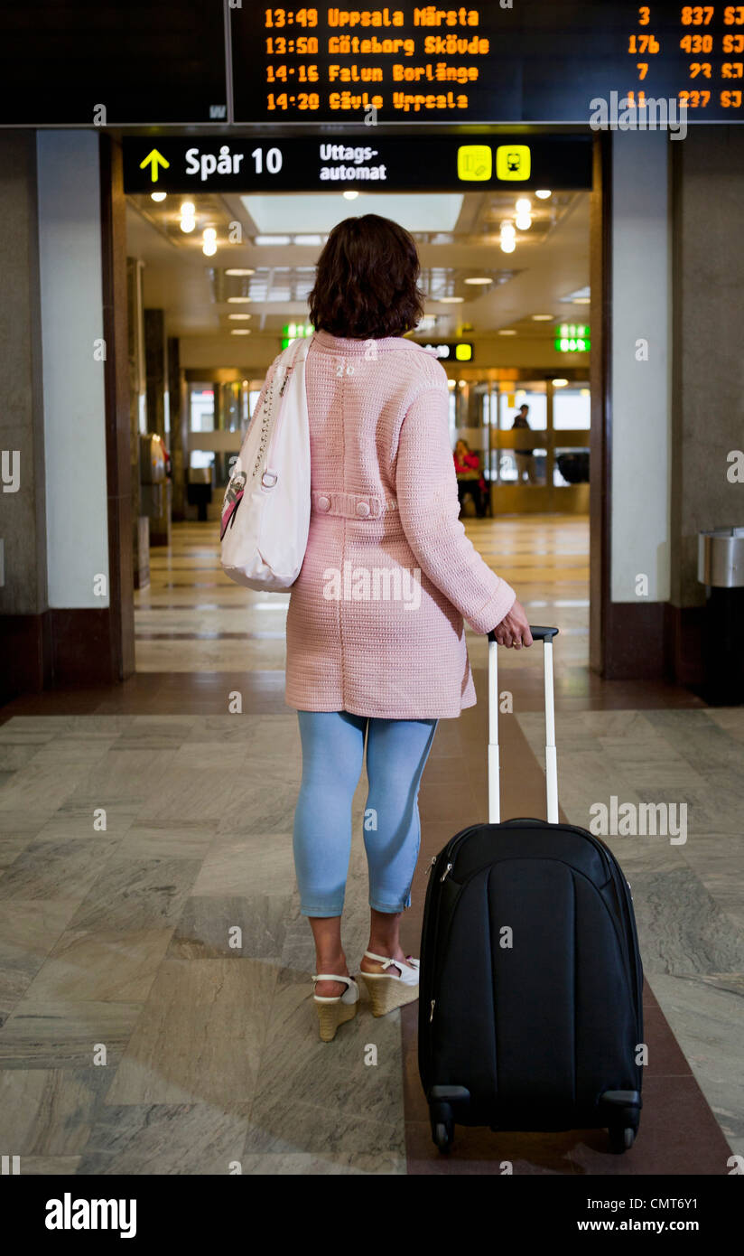 Rear view of woman standing by information panel - Stock Image