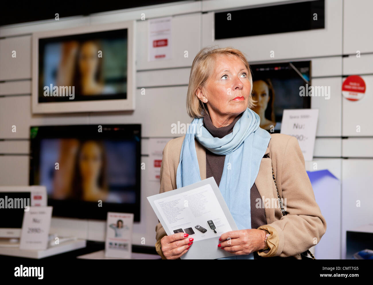 Woman holding product brochure at TV store - Stock Image