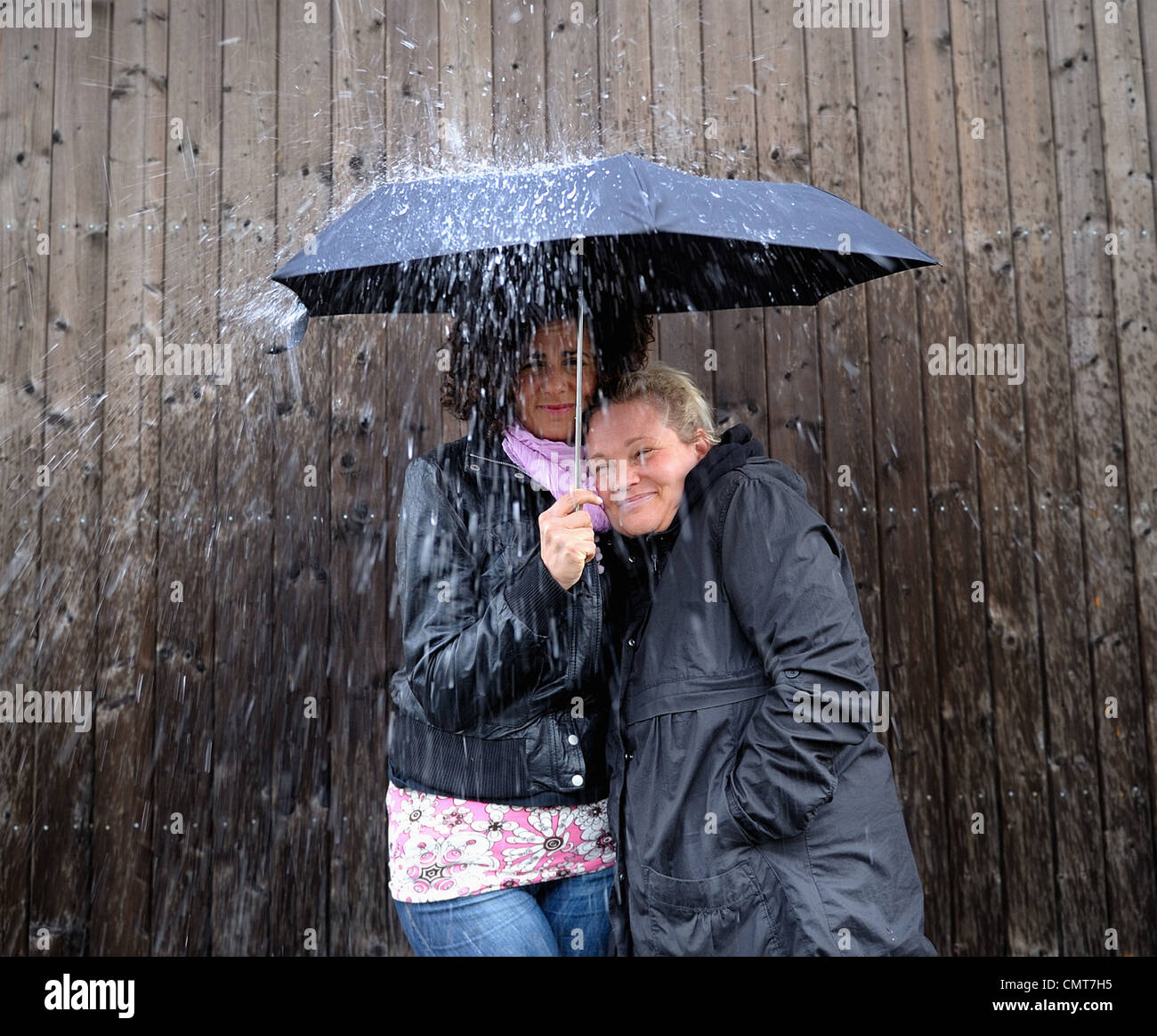 Two women under one umbrella - Stock Image