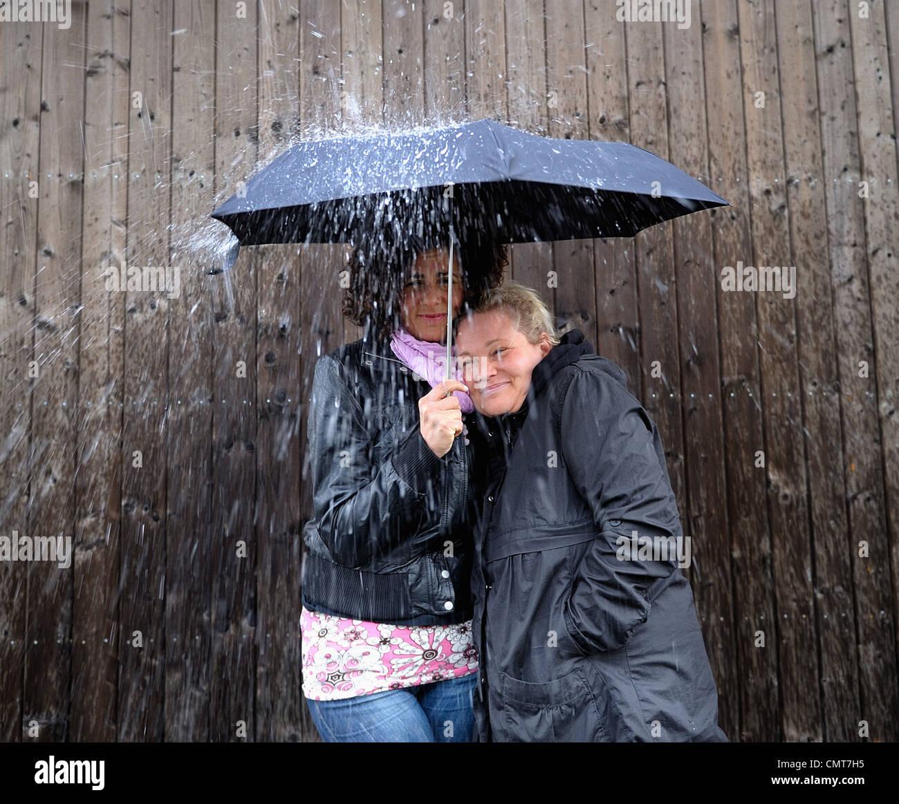 Two women under one umbrella Stock Photo
