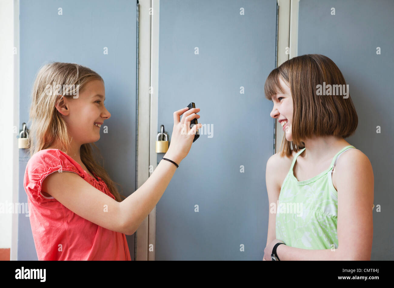 Girl showing something to her friend on mobile phone - Stock Image