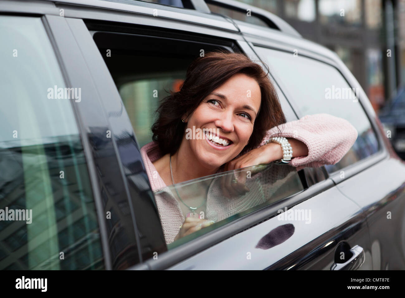 Woman leaning out from car window - Stock Image