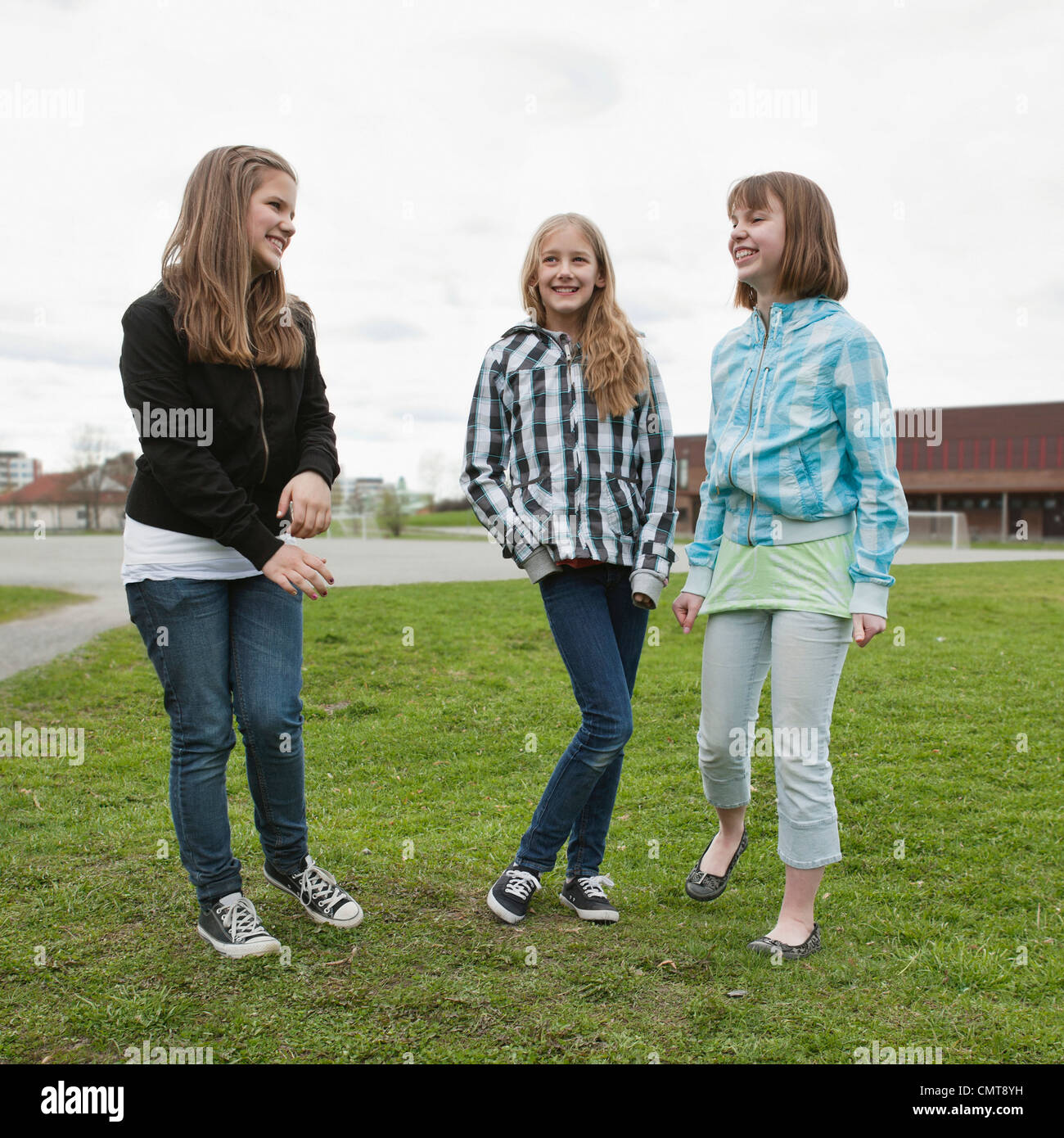 Three friends (12-13) spending time in lawn - Stock Image