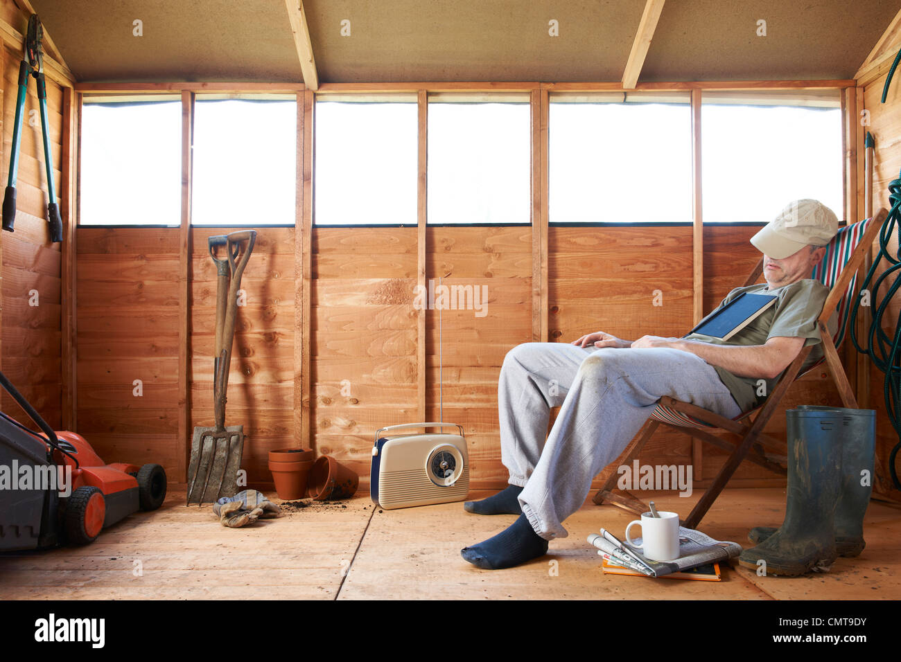 Man sitting in deckchair falling asleep in the shed - Stock Image