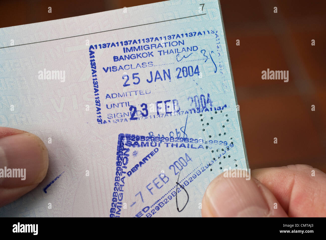 Entry and exit visa stamps of Thailand on a page in a passport - Stock Image